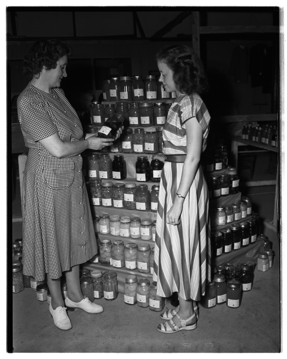 Mrs. Ruth Saunders, Fayette home demonstration agent, and her assistant, Mrs. Mary Helen Horn, preparing exhibit for…