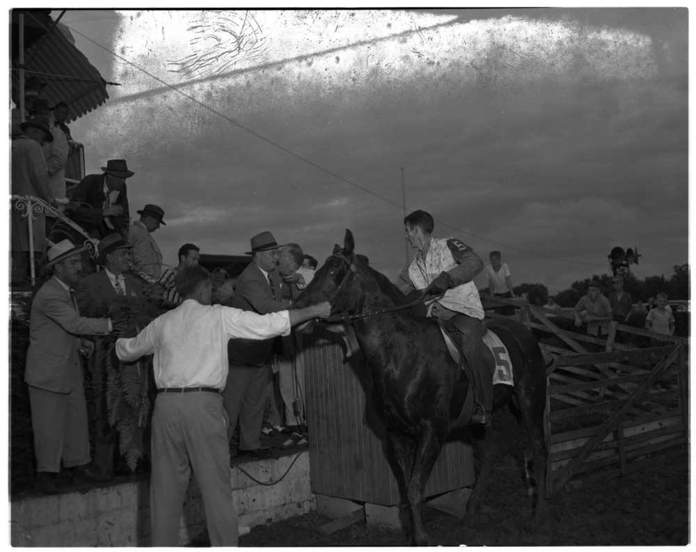 Pictured in connection with running of 1949 Plug Horse Derby. Governor Earle C. Clements handing winner's trophy to…