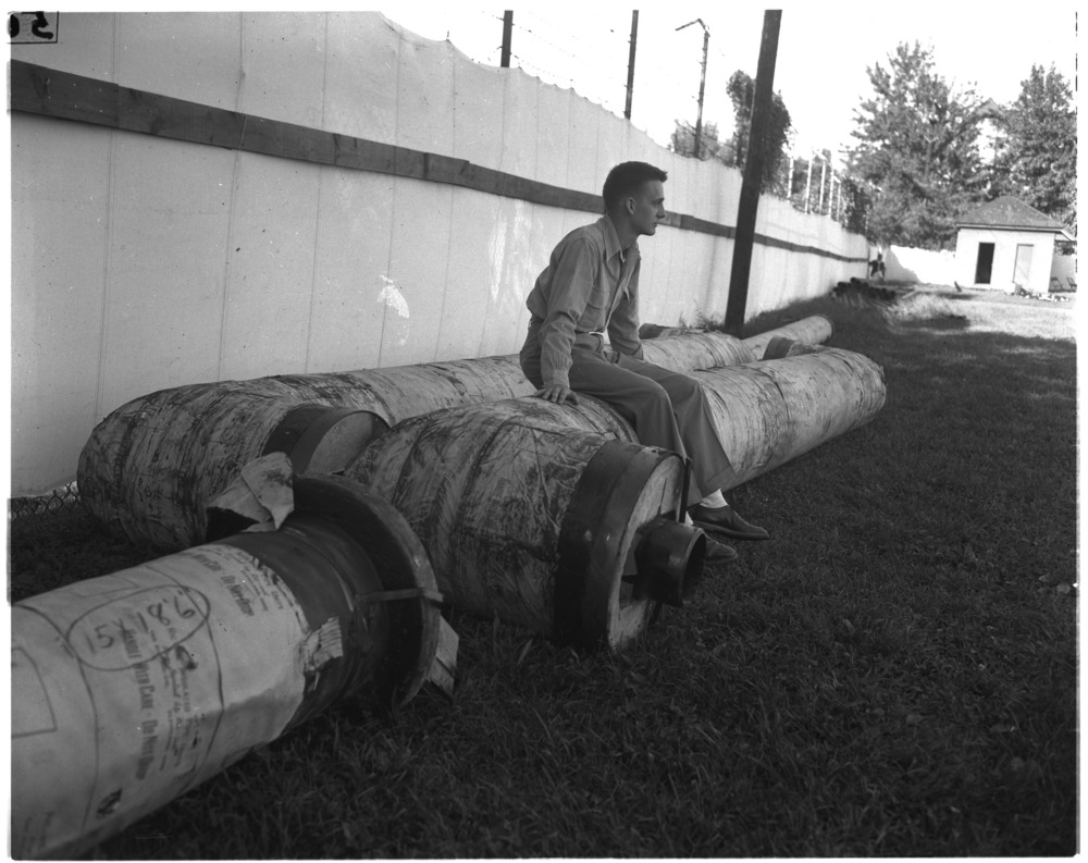 Charles Dorroh, University of Kentucky  senior, sitting on section of pipe that will feed steam to Memorial Coliseum