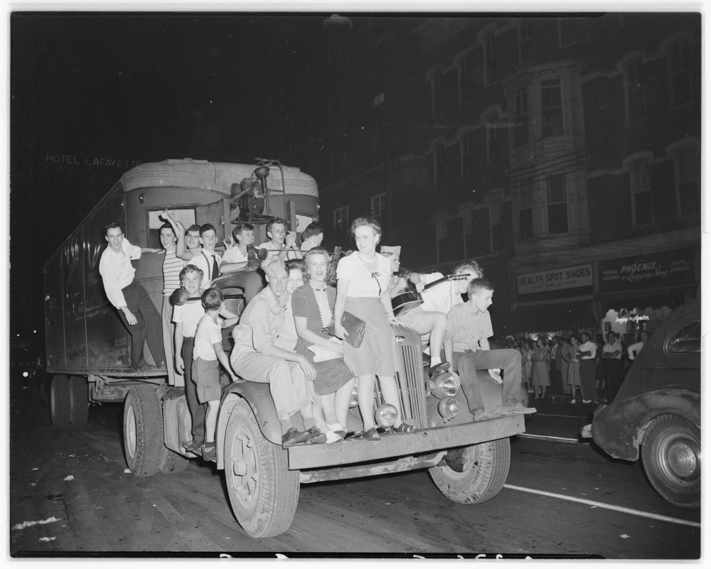 V-J Day Celebration in Lexington.  Shot of Victory demonstration; group of youths piled on truck.  They had commandeered…